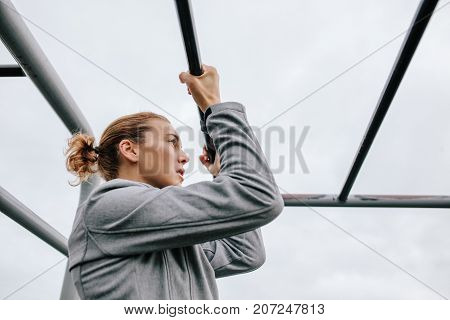 Athletic Woman Exercising Outdoor On Fitness Equipments