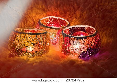 A beautiful candlestick ball of multi-colored glass with rays of light, with a glowing candle inside