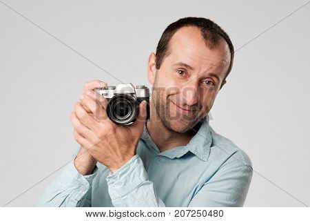 Mature caucasian man in blue t-shirt studing to use digital camera. He is smiling looking at us