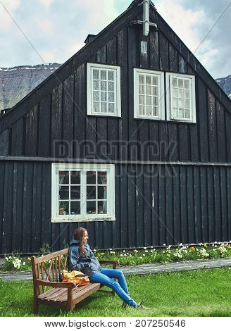 woman traveler sitting on a bench near a wooden village house in Iceland.