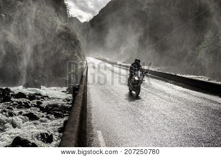 Motorbike driving fast on wet canyon valley road and bridge across river. Norway.