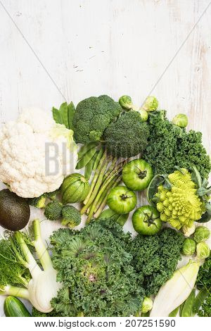 Assortment of green vegetables on the white wooden table, copy space for text on the left, vertical, top view, selective focus