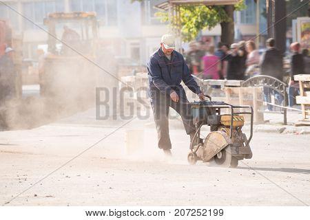 Uzhgorod,ukraine - September 28, 2017: Worker Cutting Concrete Road With Diamond Saw Blade Machine I