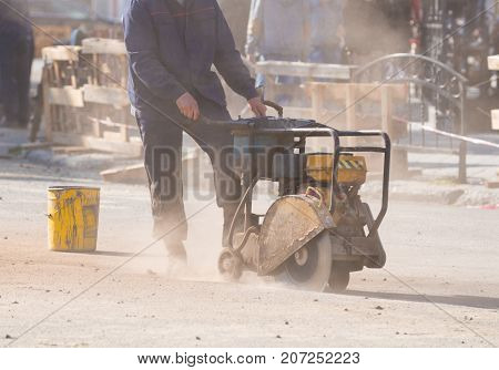 Worker cutting concrete road with diamond saw blade machine. Road reconstruction