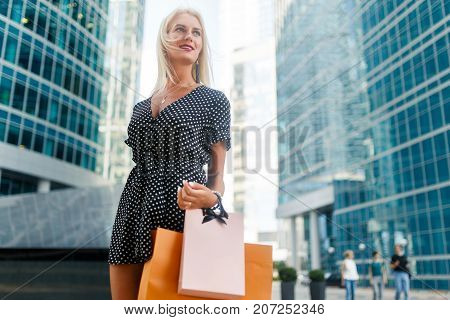 Photo of young blonde in dress with purchases on city street near modern buildings