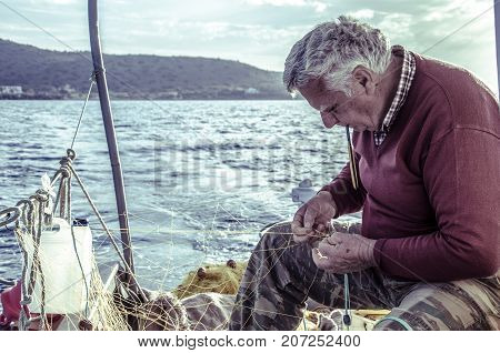 Milatos, Crete, Greece - April 23, 2016; An old fisherman repairs his fishing net on the boat as he goes for fishing.