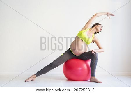 One young pregnant woman doing fitness exercises at studio