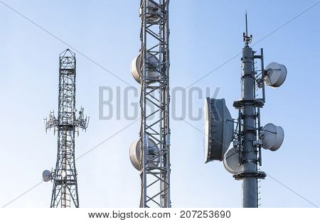 Broadcast relay station antennas at rising. Telecommunications towers with blue clear sky.