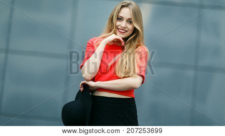 Photo of smiling girl in red jacket against gray wall of building