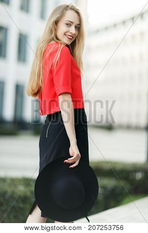 Photo of smiling girl in a red jacket with hat in hand against a gray wall of a building