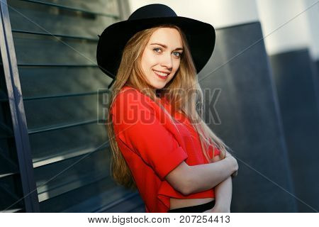 Photo of smiling blonde in black hat near wall of building