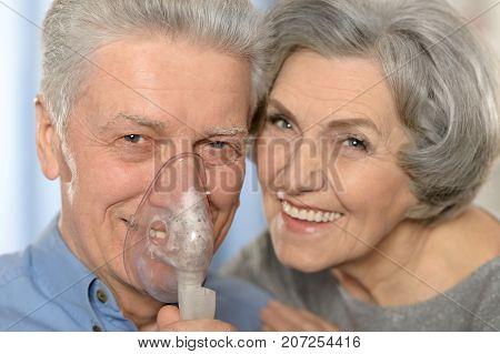 Portrait of an ederly couple making inhalation