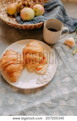 two croissants on a plate with a glass of tea