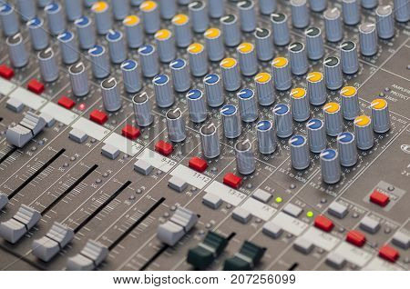 Close-up on knobs of an audio console. Digital audio board. Studio workstation. Mixing console.