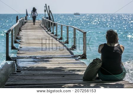 Relaxing on the beach. women sitting alone on a the wooden bridge on the sea.