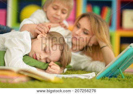 mother and sons doing homework while lying on floor in room