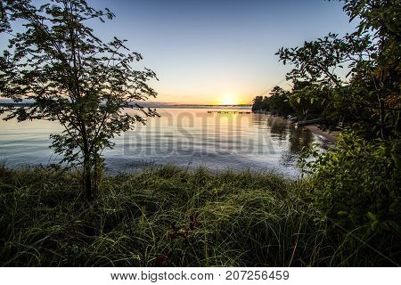 Wilderness Lake Sunrise Background.  Dawn over the horizon of Lake Superior with a dock and sunrise at the background