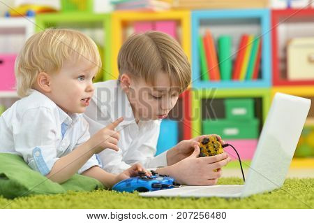 two boys playing computer games on laptop