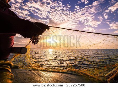 Fisherman's hand silhouette  throwing fishing net at sunset, Crete, Greece on July 20, 2017.