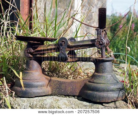 rusty iron weighing scales in a rural setting outdoors