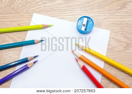 Different colored pencils paper sheet and pencil sharpener lie on wooden table. Photo with space for text. Seven pencils of rainbow colors. Copyspace. Back to school. Wooden background.