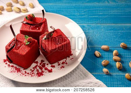 Three red velvet cakes on white plate on a blue wooden background. Still life. Food