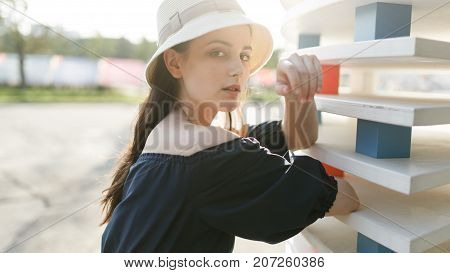 Photo of girl in hat and black dress in modern building on summer day