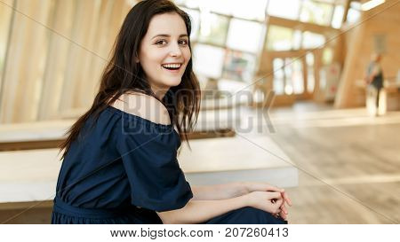 Photo of smiling girl in black dress in building on blurred background