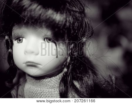 Anti children violence family problem campaign concept : cute girl child doll crying with blood of tear from family social violence. black and white color