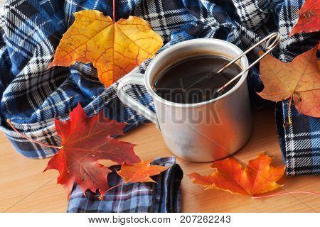 Tea mug handkerchief and autumn leaves on the table