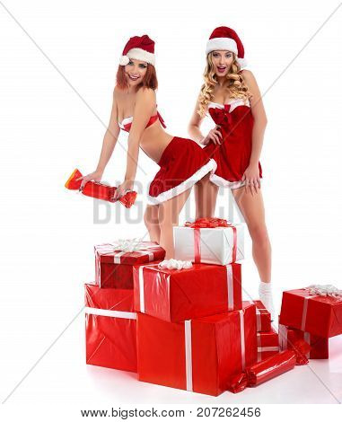 Seductive Santas. Studio shot of two gorgeous young sexy women wearing Christmas outfits standing in a pile of presents isolated 2018, 2019.