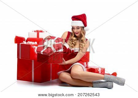 Sexy Santa girl. Horizontal portrait of an attractive blonde woman wearing seductive Santa Claus outfit opening her present looking excited isolated. 2018, 2019.