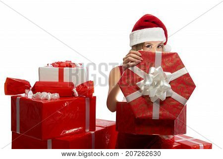 Eyes full of Christmas joy. Studio shot of a young female dressed in Santa Claus outfit opening a gift peeking out from behind the gift box to the camera isolated. 2018, 2019.