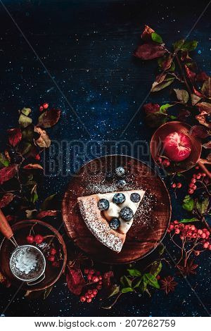 A piece of pumpkin pie with blueberries and persimmon on a dark wooden background with floral decoration. Autumn flat lay with copy space. Conceptual stylised food still life, food and drink table top shot on dark background.