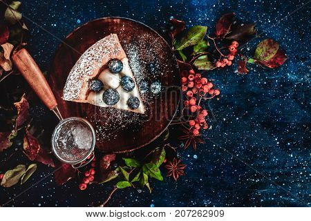 Close-up of a piece of pumpkin pie with powdered sugar and a strainer on a wooden plates. Handmade dishes in autumn flat lay. Conceptual stylised food still life, food and drink table top shot on dark background. Copy space.