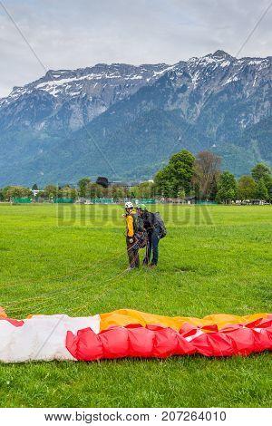 Interlaken Switzerland - May 26 2016: Tandem paraglider after landing against the background of the Swiss Alps in Interlaken Switzerland.