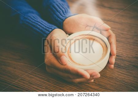 Close up female hand holding cup of cappuccino coffee on wooden tabletop for relax