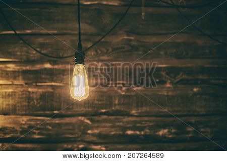 Light Edison bulb on dark wooden background. vintage effect