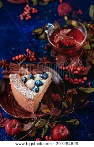 Close-up of a piece of pumpkin pie with powdered sugar in a dark autumn still life with smoke. Sweet Halloween concept with copy space. Conceptual stylized food still life with autumn leaves and berries. Copy space.