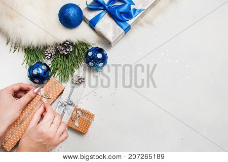 Holiday preparation. Christmas and New Year. Unrecognizable woman wrapping present boxes, handmade decoration, ornament blue balls and pine branch laying on table nearby, top view with copy space