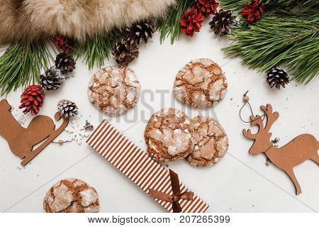 Festive background of Christmas and New Year. Decoration from pine branch with strobila, wooden deer and skate, sweet cakes and present, top view. Holidays, congratulation and homemade decor concept