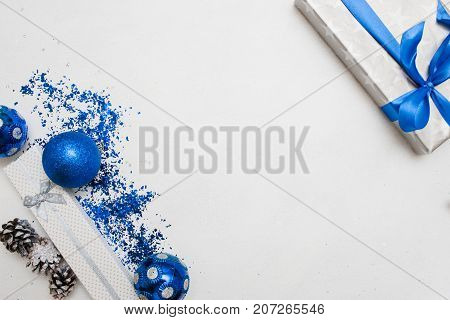 Festive background of Christmas presents. Wrapped in silver paper gifts, ornament blue balls on white table with spangles spread around, top view and copy space in middle. Handmade decoration concept
