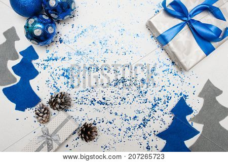 Background of Christmas decor and gifts. Wrapped in silver paper present, ornament blue balls and felt fir tree with spangles spread around, top view and copy space. Handmade decoration concept