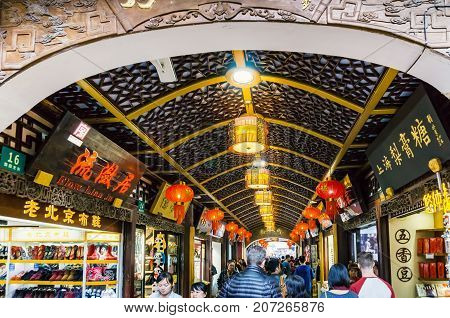 Shanghai, China - Nov 4, 2016: On Yu Yuan Old Steet - Area bustling with people and activities. The stores around this area are constructed in classical or traditional Chinese architectural design, featuring an ornate ceiling.