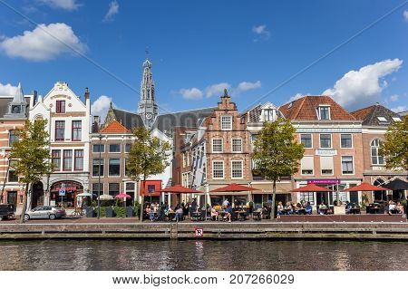 HAARLEM, NETHERLANDS - SEPTEMBER 03, 2017: People enjoying the sun at a historic canal in Haarlem Netherlands