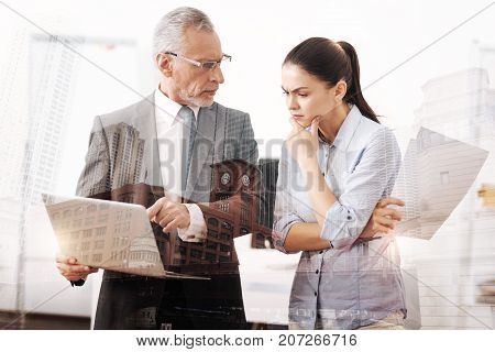 Rigid rules. Professional strict male boss holding laptop and talking with a young concentrated woman while working on the project