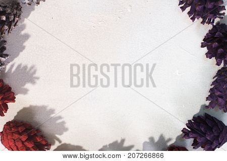 Festive background of Christmas decoration. Top view colorful strobilas on white backdrop, free space in middle. Winter holidays, celebration and New Year decor concept