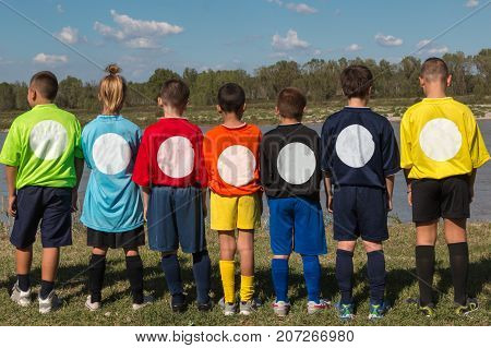 Children in Line Back Turned with Shirts with Different Colors on the Edge of River