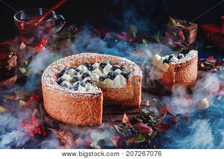 Cut cake with a shortbread crust on a dark background. A piece of cake with whipped cream and blueberries on a wooden plate. Dark food photography with smoke. Pumpkin pie in a Halloween still life with pastry. Contrast colors and soft focus.