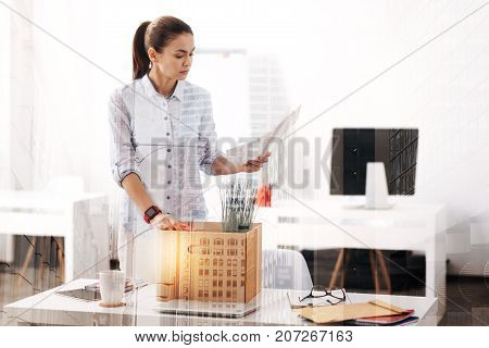 Change your job. Unemployed young cheerless woman holding papers and packing her belongings while standing in the office
